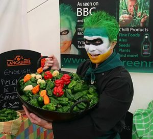 RK Alker Funny Kids Author as The Chilliman from Little Green Men Chilli holding a karai pan full of red hot chili peppers