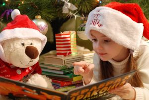 A young female child reading a Christmas book with her cuddly Christmas toy with RK Alker Children's Author of Funny Kids Books