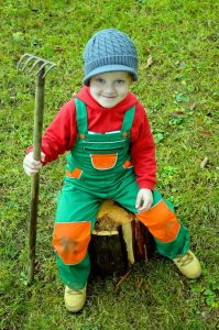 a cute kid witha garden rake doing Kids Gardening RK Alker Children's Author Chilliman Grower Food Evangelist Cook from Little Green Men Chilli, Chorley, Lancashire, England, UK, Tel. 01772970190